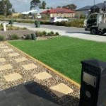 Prestige 38mm artificial lawn in  Rockingham with cream concrete kerbing, stepping stone and decorative stones by go Greener Synthetics